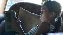 A cute little 13 year old Asian girl uses her tablet alone in the living room.