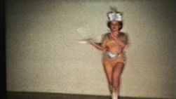 A beautiful teenage girl does her dance routine complete with baton and marching boots.