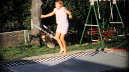 A teenage girl has fun jumping on an in ground trampoline in the back yard in the summer of 1967.