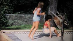 Teenage girls have fun jumping on an in ground trampoline in the back yard in the summer of 1967.