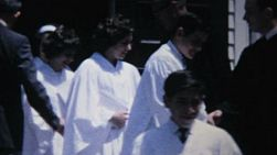 A group of high school aged teenagers leave the church after their first communion service in 1967.