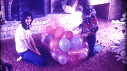 Two teenagers unpack a big bag of balloons as they get ready to celebrate a special birthday during Christmas of December 1974.