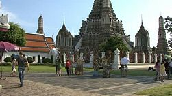 "A tilt up shot of Thailand's famous Wat Arun or ""Temple of the Dawn"" along the banks of the Chao Phraya river in Bangkok, complete with tourists wandering around the grounds."