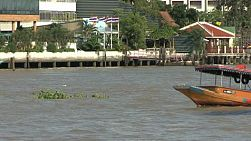 An old Thai boat bobs and weaves on the busy Chao Phraya river in Bangkok, Thailand.