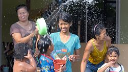 Bangkok, Thailand - April 14, 2014: Thai Children and family splashing water around during a water fight as part of the annual Songkran Festival in Thailand.