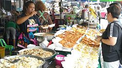 A Thai vendor sells her delicious Thai food to tourists shopping at the market in Bangkok, Thailand.