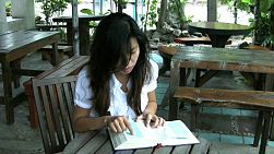 A Thai girl sits down to read and study her Bible in Bangkok, Thailand.