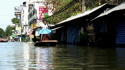 A Thai man uses a pole to navigate himself down a flooded street while his wife hides under an umbrella during the floods in Bangkok, Thailand.