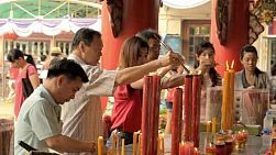 BANGKOK, THAILAND  - FEBRUARY 9, 2013: Thai people lighting candles  at a shrine to Kwan Yin (Kuan Im) on the eve of Chinese New Year in Chinatown, Bangkok, Thailand.