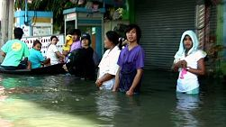 A group of Thai people stand in flood waters waiting for water taxis to take them to their homes in Bangkok, Thailand.