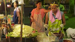 A Thai street vendor preparing to make Som Tum or papaya salad in Bangkok, Thailand.