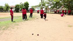 A group of female Asian students play a game of Bocci ball during a break at school in Buriram, Thailand.