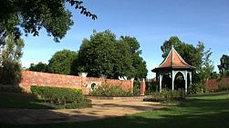 A tilt down shot of a lovely Thai gazebo or sala near a brick wall in a park in Bangkok, Thailand.