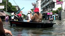 Three Thai women do their best to navigate their plastic boat in the flooded streets of Bangkok, Thailand in the fall of 2011.