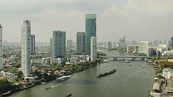 Time lapse of the Saphan Taksin bridge crossing the Chao Phraya River in Bangkok Thailand, with hotels and apartment buildings along the river banks.