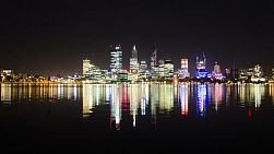 Time lapse of the Perth City skyline at night, reflecting on the waters of the Swan River.