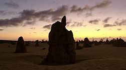 Time lapse of a silhouette of the pinnacles at sunset, with storm clouds brewing in the sky. the pinnacles are limestone formations contained within Nambung National Park, near the town of Cervantes, Western Australia.