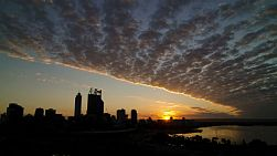 Time lapse of sunrise over Perth City skyline with a band of clouds moving over.