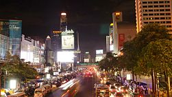 BANGKOK, THAILAND - NOVEMBER 8, 2013: Time lapse of busy traffic at night on Ratchadamri Road, next to Central World, in Bangkok, Thailand. Baiyoke Tower can be seen in the background.