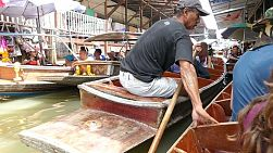 Tourists enjoy riding in long tail boats and shopping at the famous Damnoen Saduak Floating Market in Ratchaburi, Thailand.