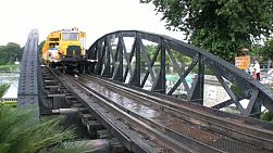 An old historical tourism train crosses the famous railroad bridge over the river Kwai in Kanchanaburi, Western Thailand.