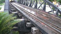 A tilt up shot of a tourist train crossing over the famous railroad bridge on the river Kwai near Kanchanaburi, Western Thailand,