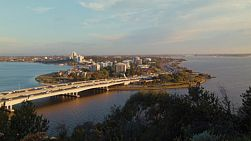 View of the Narrows Bridge over tree tops from King's Park, in Perth Australia, with the golden evening light illuminating the bridge.