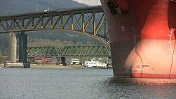 A tugboat passes under a bridge in front of a large ship moored in the harbor. (HD 1080p30)