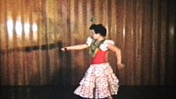 A beautiful teenage girl performs her Spanish dancing at a recital complete with many twists and twirls.