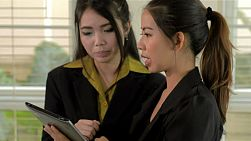 Two young asian women showing and discussing work on a tablet computer.