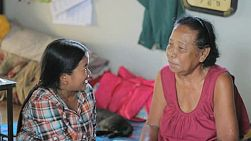 Two Thai ladies have a friendly chat in a slum home in Bangkok, Thailand.