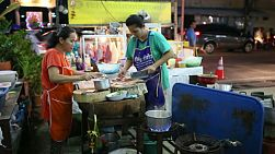 Two Thai street food vendors are busy making a tasty spicy soup at the market in Bangkok, Thailand.