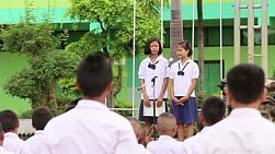 Two cute female Asian students share in a school assembly in Buriram, Thailand.