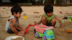 Two cute Asian boys playing nicely with each other at the beach with all their toys.