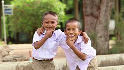 BURIRAM, THAILAND, SEPTEMBER 2013: Two cute Asian grade school students pose for the camera outside of school in Buriram, Thailand.