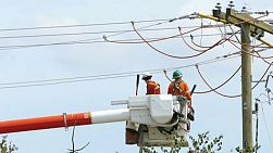 A pair of hydro repair linemen work together to resolve various issues on a telephone pole in suburbia in the city of Vancouver.