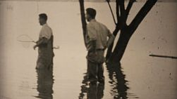 Two men try to catch fish in their flooded backyard during the floods of 1948 in Dallas, Texas.