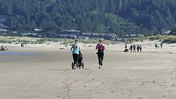 Two young mothers enjoy running on the beach in the morning even with pushing a stroller.