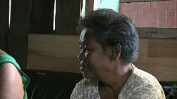 A pan shot of two elderly Thai ladies talking and visiting in the slums of Bangkok, Thailand.