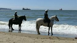Two police officers on horseback patrol a busy beach on a gorgeous summer day in Vancouver.