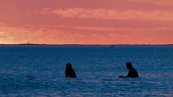 Silhouettes of two surfers waiting for a wave at South Cottesloe Beach in Western Australia, as the sun sets in the background.