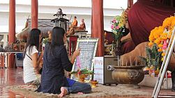 Two women pay their respects at a Buddhist temple in Bangkok, Thailand.