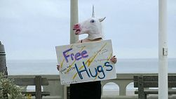A cute lady dressed up as a unicorn dances and offers free hugs to the public.