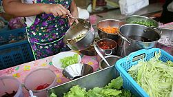 "A vendor making ""Yam Mamuang"" or spicy Thai mango salad at a stall in Bangkok, Thailand."
