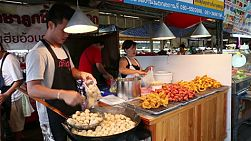 Vendors frying pork balls, small sausages, and other snacks at a stall in a market in Bangkok, Thailand.