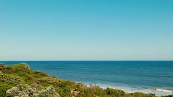 View across a dune covered in bushes and plants, to the clear waters and horizon of the Indian Ocean.