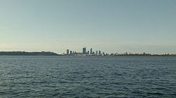 View across the waters of the Swan River in Western Australia, with the skyline of the City of Perth on the horizon.