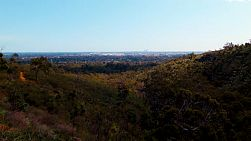 View west from the Darling Scarp, across hills and valleys, towards the flat plains of Perth, with the Perth CBD skyline in the far distance.