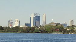 Perth City skyline framed by the swan river and trees, looking across East Perth.