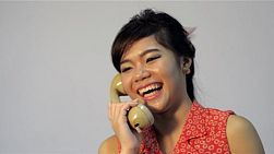 Vintage dressed young asian woman happily talking on the phone - tracking shot.